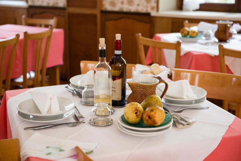 tavolo apparecchiato con piatti, vino e frutta