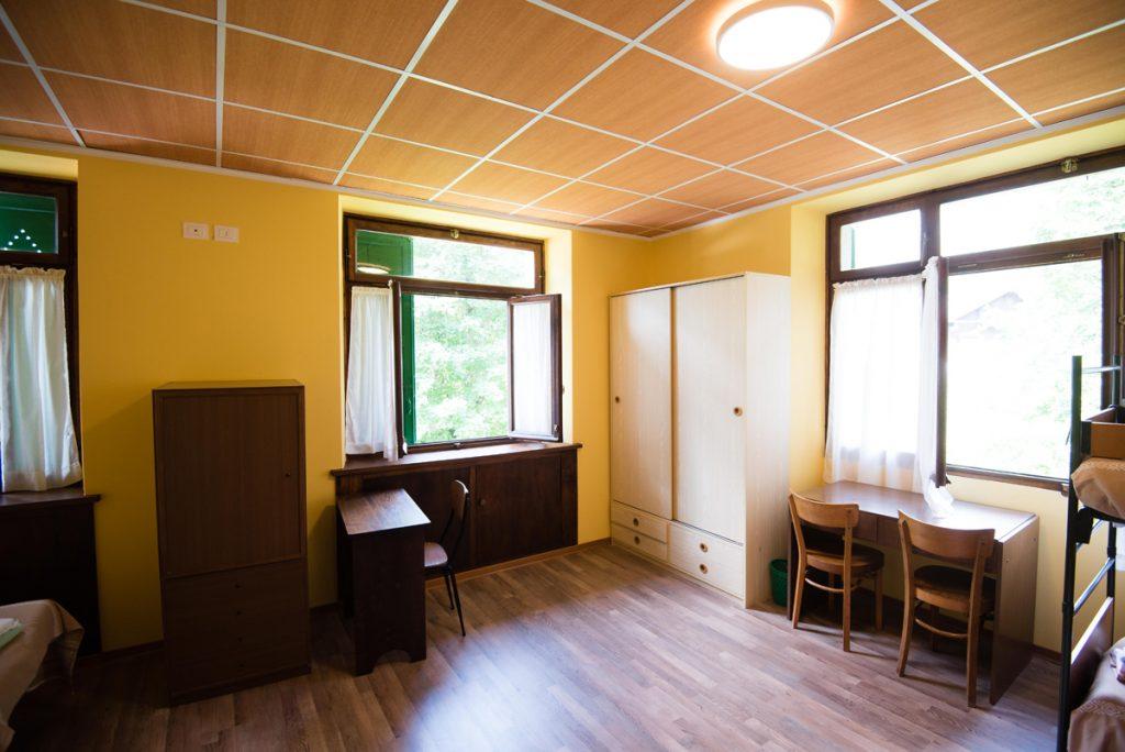 camera con scrivania, sedie, finestre