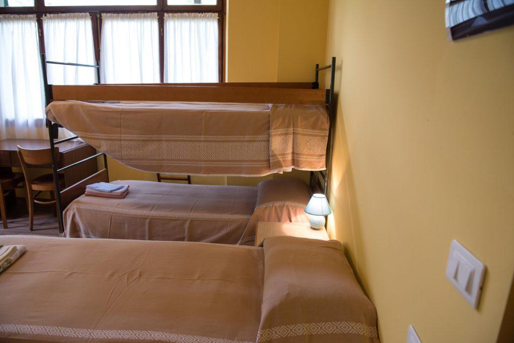 camera con 3 letti e finestre