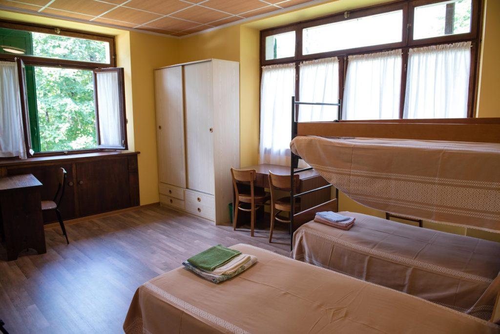 camera con 3 letti, finestre e armadio