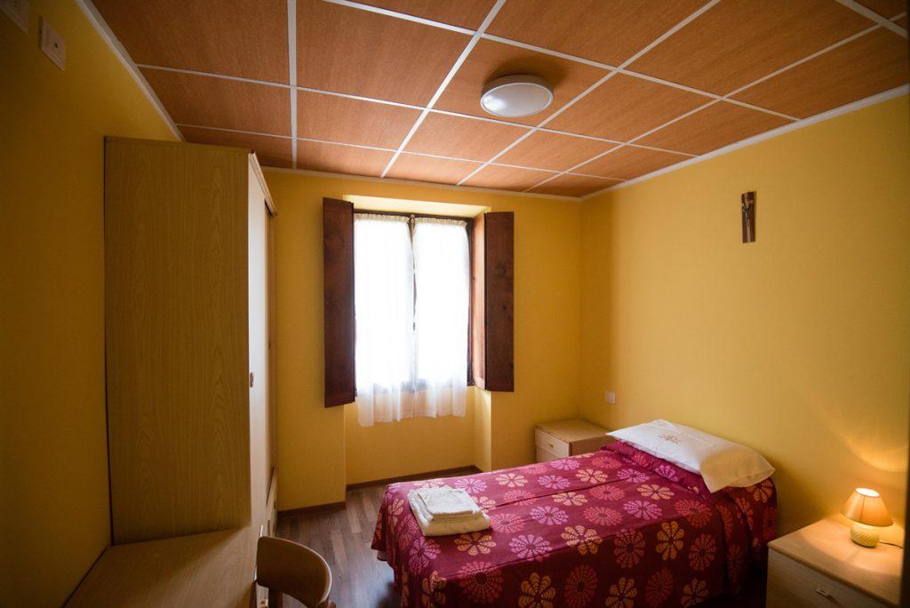 Camera con letto singolo e pareti gialle